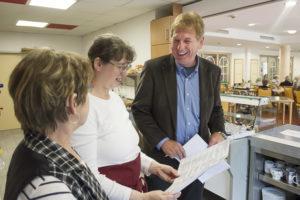 Anja Grune, Helga Mai und Willi Stüwer stehen zusammen hinter er Theke. Sie lesen auf einem Zettel nach, was sich die Bewohner zu Mittag zu Essen wünschen und haben sichtbar Spaß.