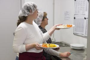 Mitarbeiterinnen des DFG Hagen schauen auf eine Liste. Eine Mitarbeiterin hält bereits das fertige Essen in den Händen.