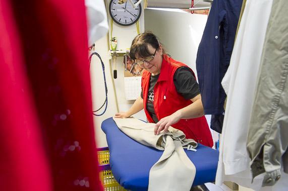Eine Mitarbeiterin der Wäscherei Kreft faltet gebügelte Wäsche.
