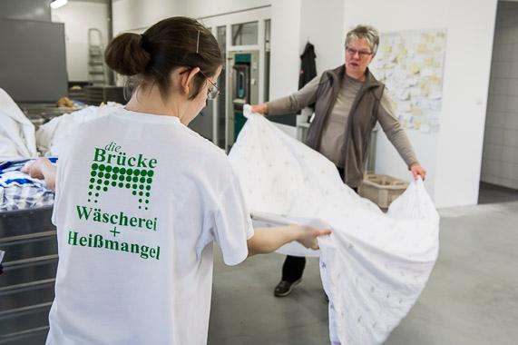 Adelheid Hoffbauer faltet zusammen mit einer Mitarbeiterin ein großes Betttuch zusammen.