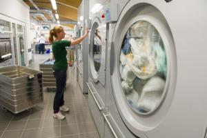 Die Tochter der Geschäftsführerin bedient gerade eine große Waschmaschine.