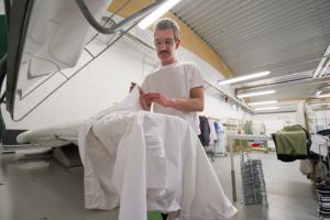Einer der wenigen männlichen Mitarbeiter beim Bügeln eines Hemdes.