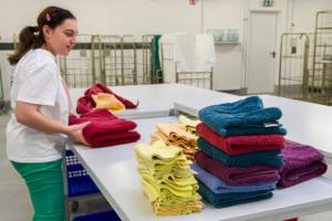 Eine Mitarbeiterin faltet bunte Handtücher und legt sie auf Stapel.