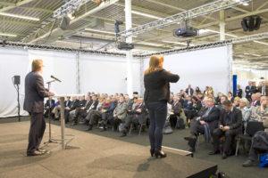 Auf der Hauptbühne spricht ein Mann vor sitzendem Publikum. Eine Gebärdendolmetscherin übersetzt simultan.