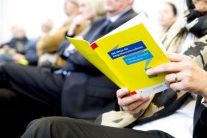 Nahaufnahme des Programms zur LWL-Messe 2014, das von einer Zuhörerin im Publikum studiert wird.