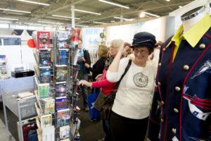 Eine Frau probiert am Stand des Second-Hand-Shops von HFR-Rümpelfix einen Hut an und freut sich.