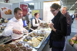 Eine Besucherin lässt sich an der Kuchentheke die Auswahl zeigen.