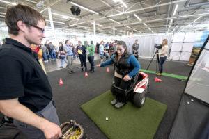 """Bei einer Mitmachaktion hat sich eine Besucherin in einen flexiblen Rollstuhl gurten lassen, mit dem sie ohne Beinkraft """"aufstehen"""" und Golf spielen kann."""