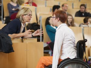 Eine Professorin der Europa-Universität in Flensburg tauscht sich im großen Vorlesungssaal mit einer Bildungsfachkraft im Rollstuhl aus.
