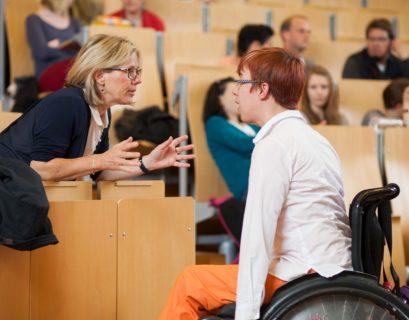 Eine Professorin tauscht sich am Podium in einem vollen Vorlesungssaal mit einer Bildungsfachkraft im Rollstuhl aus.