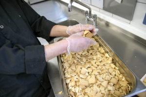 Mitarbeiter Rolf Adämmer zerkleinert mit Handschuhen Butterkekse über einer großen Wanne, die schon fast voll ist. Es sind nur seine Hände und die Wanne zu sehen.