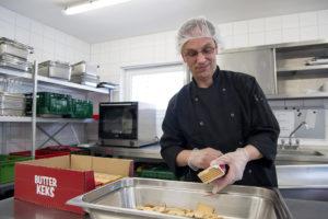 Rolf Adämmer öffnet eine neue Packung Butterkekse, um sie zu zerkleinern.