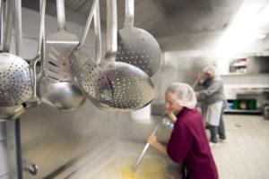Im Vordergrund Küchengeschirr, dahiner eine Frau mit Haube, die mit einem großen Löffel in einer riesigen Kochwanne rührt.
