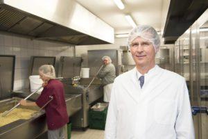 Bestfood-Chef Jürgen Groth steht mit Schutzhaube und Kittel in seiner Großküche.