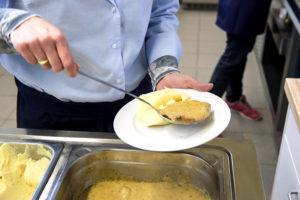 Eine Servicekraft schöpft das Mittagsmenü aus den Warmhaltewannen auf einen Teller. Es sind nur die Hände und der Teller zu sehen.