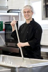 Rolf Adämmer rührt mit einem großen Schneebesen in einer Wanne voller Joghurt und lächelt in die Kamera.