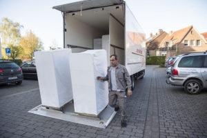 Ali Cütcü neben zwei weißen Wäschecontainern, die er gerade ausgeladen hat.