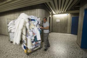Ali Cütcü rollt einen mannshohen Gitterwagen mit schmutziger Wäsche durch den Kellerflur eines Gebäudes.