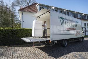 Der Grenzland-Mitarbeiter schiebt einen weißen Wäschecontainer aus dem Lkw auf die Laderampe hinaus.