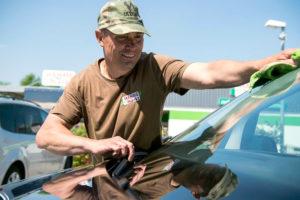 Ein Mitarbeiter des Servicehauses beim Reinigen einer Autoscheibe.