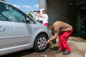 Zwei Mitarbeiter des Servicehauses Stemwede reinigen ein Auto: Einer betätigt einen Hochdruckreiniger, der andere wäscht die Felgen.