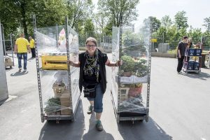 Katharina Wodrich zieht mit der linken und der rechten Hand je ein Rollregal mit Arbeitmaterial über einen Hof mit sich und geht dabei auf die Kamera zu.