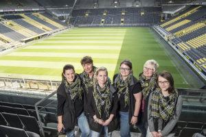 Das Team des Blumengeschäfts auf der BVB-Tribüne, im Hintergrund das noch leere Spielfeld.