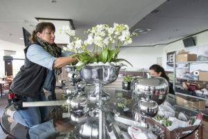 Die Inhaberin Birgit Honvehlmann steckt einen Strauß aus weißen Blumen in einem silbernen Kelch zusammen.
