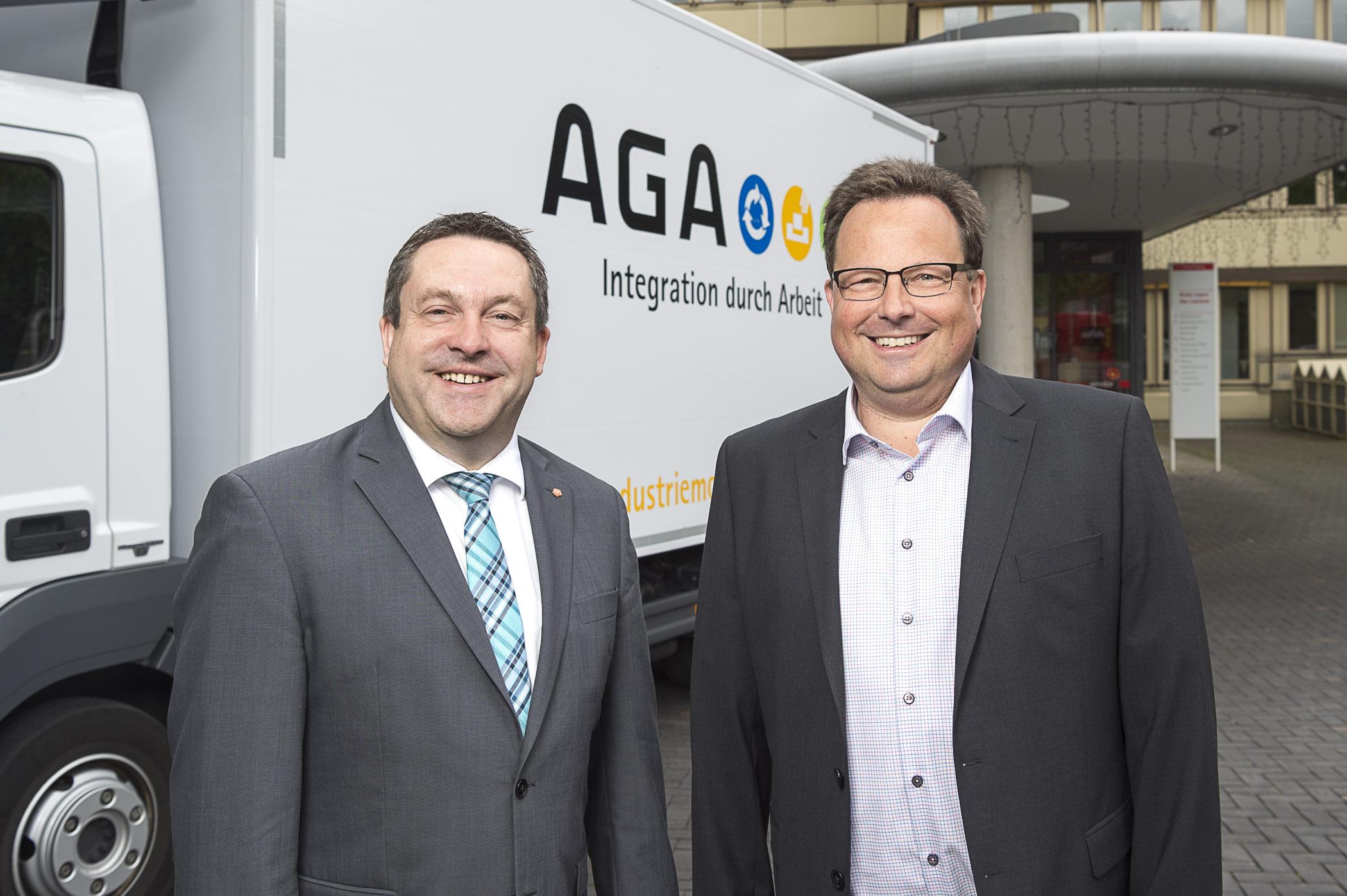 Landrat Dr. Axel Lehmann und Geschäftsführer Jens Filies stehen vor dem Firmen-LKW und lächeln in die Kamera.