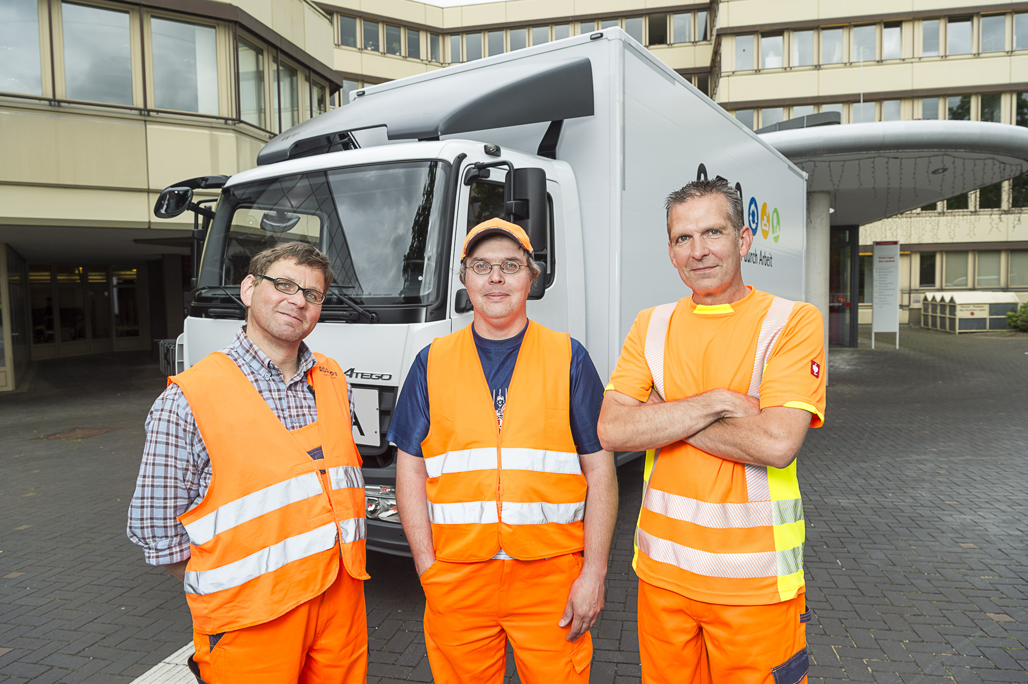 Die Mitarbeiter Björn Richter, Klaus-Dieter Weiß und Frank Garz stehen in voller Arbeitsmontur vor dem Firmen-LKW.