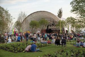 Bei gutem Wetter sitzen und stehen Menschen auf einer Wiese vor einer überdachten Bühne. Foto: BUGA Heilbronn 2019 GmbH