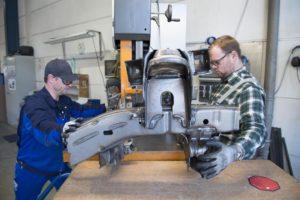 Zwei Mitarbeiter bedienen gemeinsam ein großes Industriegerät