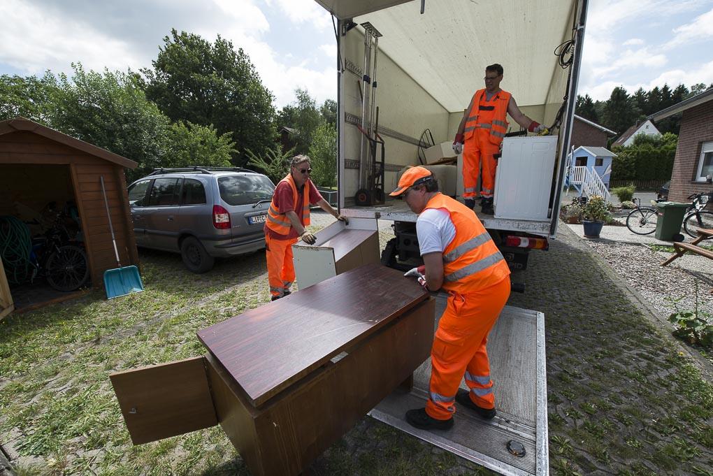 Drei Mitarbeiter der AGA in orange-farbenen Westen laden einen Schrank vom Sperrmüll in ihren Lieferwagen.