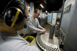 Zwei Mitarbeiter, die einen Ohrschutz tragen, sortieren Metallfedern in eine Schleifmaschine.