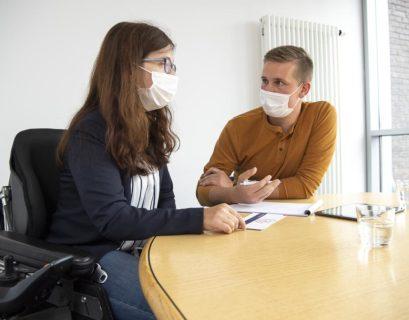 Eine Frau mit Rollstuhl sitzt an einem runden Tisch und ist gerade im Beratungsgespräch mit einem Jobpiloten. Sie schreibt auf einem Notizblock mit.