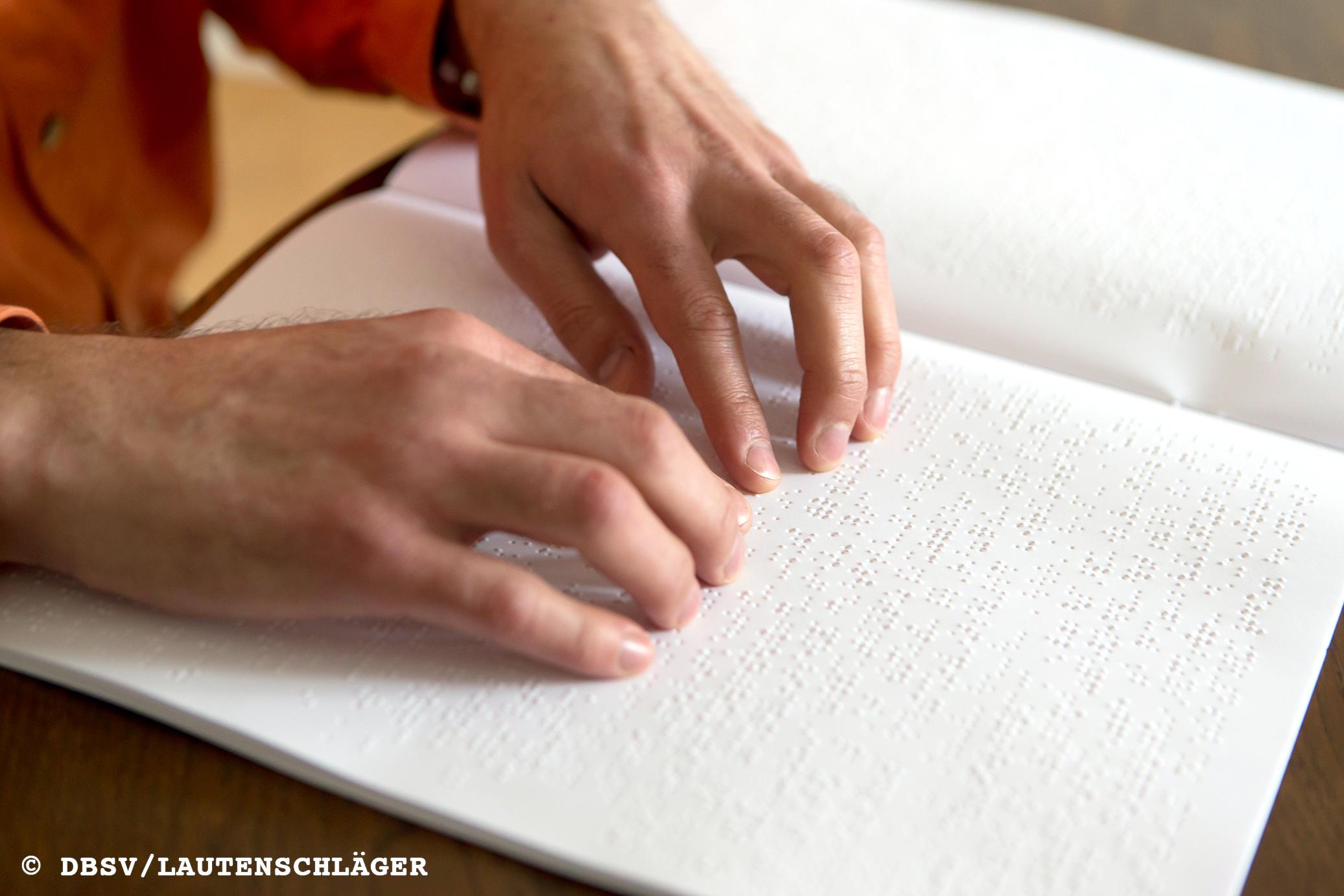 Auf dem Foto sind zwei Hände zu sehen, die ein Heft mit Brailleschrift abtasten.