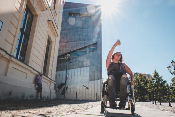 Eine Frau mit Rollstuhl reißt die Faust in die Luft, während sie an einem Gebäude vorbeifährt.