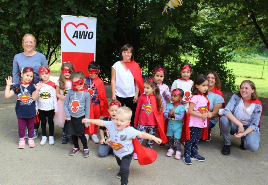 Kinder mit Superhelden-Kostümen haben sich draußen zum Gruppenfoto aufgestellt, vorne tanzt ein Kind mit rotem Umhang aus der Reihe