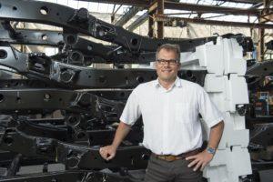 Der Geschäftsführer von Teuto InServ steht lächelnd in einer Lagerhalle vor einem Regal voller großer Autobauteile.