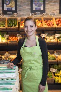 Mercedes Hamann steht mit grüner Schürze vor dem Obst- und Gemüseregal im Hofladen des Hofguts Schloss Hamborn und lächelt in die Kamera.