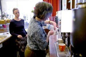 Lisa Kübler (links) schaut Ann-Sophie Bathe (rechts) dabei zu, wie sie Milch in den Tank einer großen Kaffeemaschine füllt.