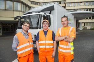 Björn Richter, Klaus-Dieter Weiß und Frank Garz (von links) stehen in orange-farbenen Arbeitswesten vor ihrem Sperrmüll-Auto.