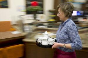 Ann-Sophie Bathe läuft mit einem Tablett voller Geschirr durch das Café Anker-Villa.