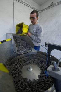 Sascha Thiele trägt eine Schutzbrille und schüttet Federn in eine Schleifmaschine.