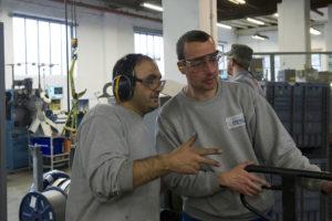 Murat Demir steht links von Sascha Thiele und erklärt ihm einen Arbeitsschritt.
