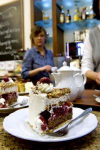 Ein Stück Kirsch-Krokant-Torte und im Hintergrund Sopie-Ann Bathe, die im Integrationsunternehmen Café Anker-Villa arbeitet.