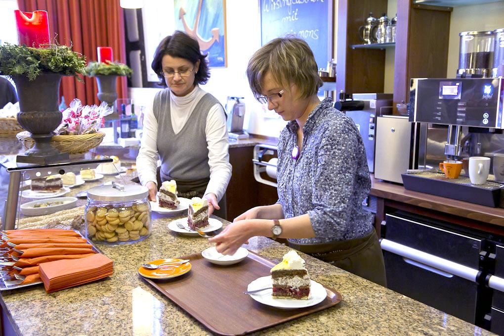 Ann-Sophie Bathe beim Anrichten von Kuchenstücken hinter der Theke des Cafés Anker Villa.