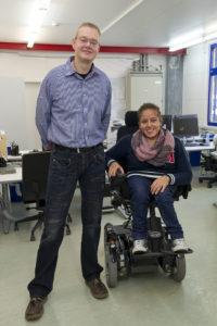 Dirk Fitscher steht neben Rafa Lawah, die in ihrem hohenverstellbaren Rollstuhl sitzt.