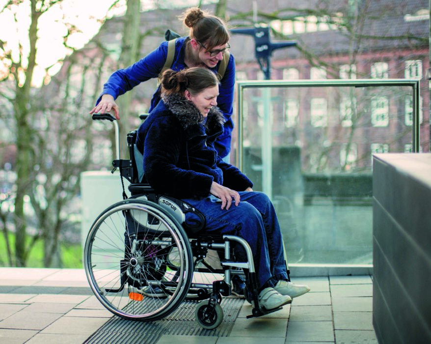 Eine Assistentin begleitet eine junge Frau mit Rollstuhl.