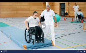 Video-Ausschnitt: Kristina Vogel mit ihrem Trainer beim Rollstuhltraining in einer Turnhalle.